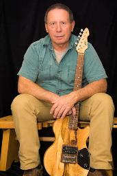Don Bastian holding carved guitar